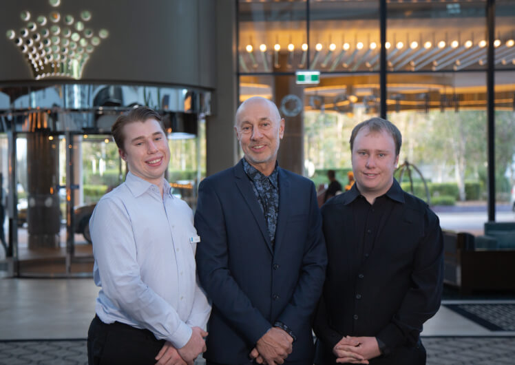 Crownability employees Ollie and Sam with their father David, standing in Crown Perth lobby